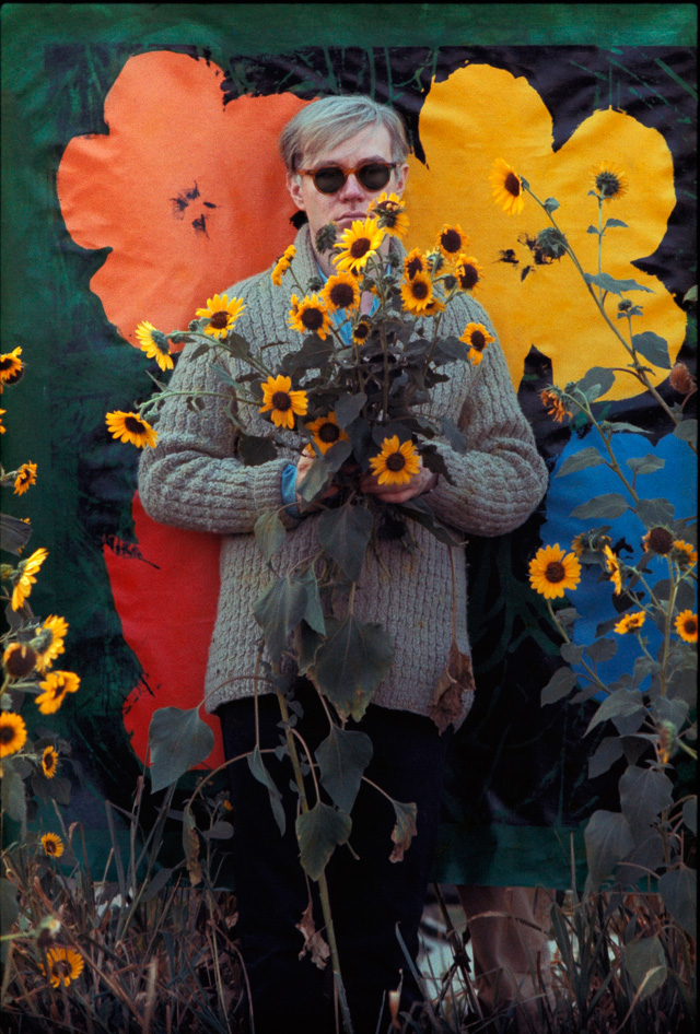 Andy-Warhol-in-a-field-of-black-eyed-Susans-holding-a-bouquet-of-flowers-with-an-early-_Flowers_-canvas-serving-as-a-backdrop-in-Queens,-New-York