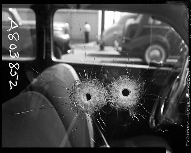 Detail of two bullet holes in car window Date: 10/10/1942 Photographer: Unknown